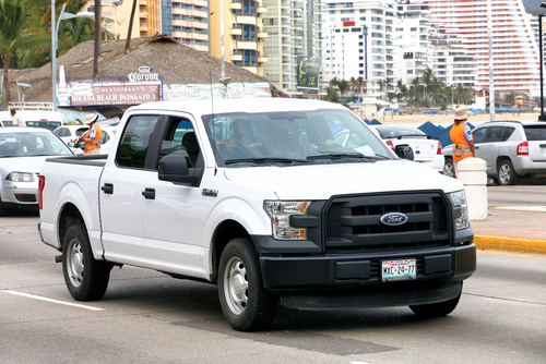 white f150 pickup truck city street