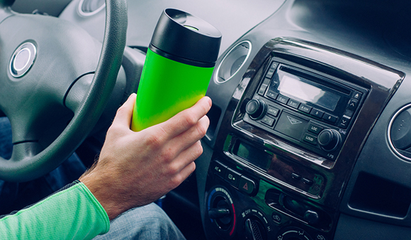 man holding travel mug in car
